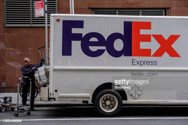A driver for an independent contractor to FedEx Corp unloads United States Postal Service bins from a delivery truck in New York US on Monday Nov 26...