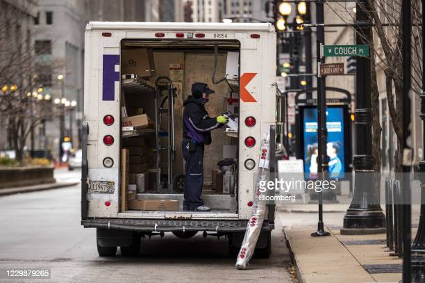 Driver for an independent contractor to FedEx Corp. Wearing a protective mask unloads a Ground truck in Chicago, Illinois, U.S., on Monday, Nov. 30,...