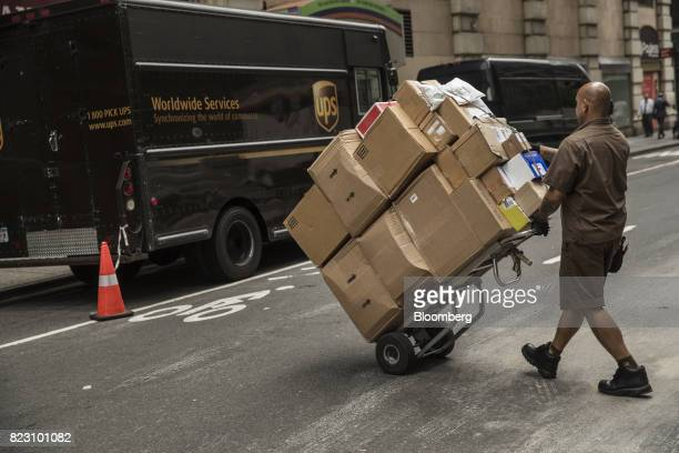 A driver for an independent contractor to United Parcel Service Inc pushes a dolly of packages towards a delivery van on a street in New York US on...