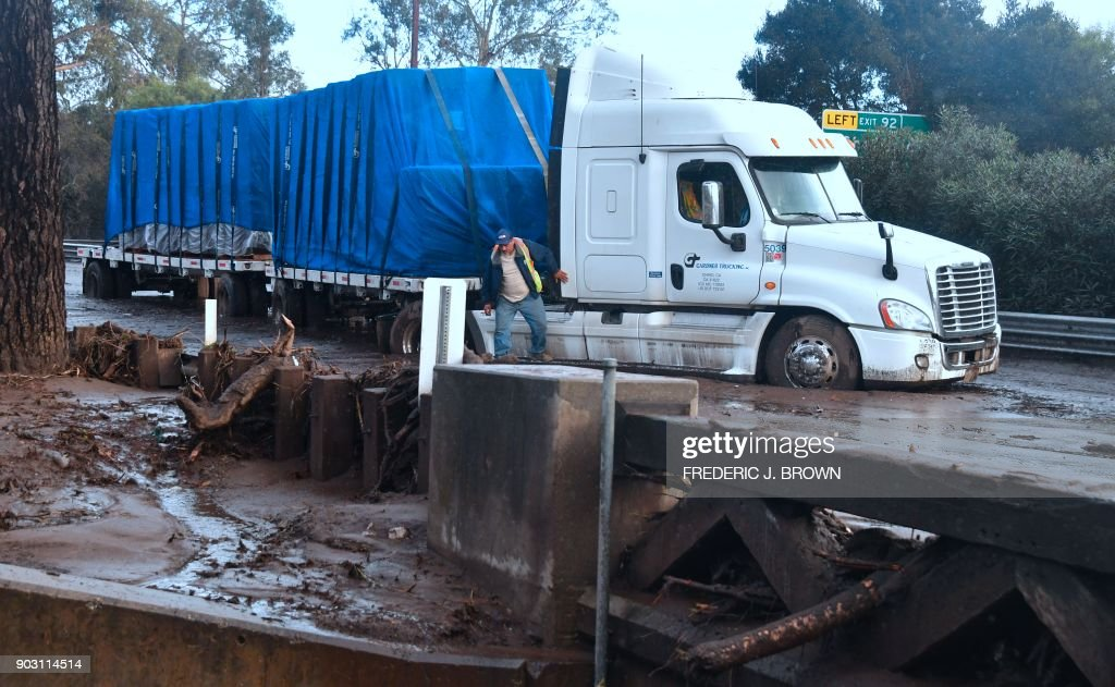 Driver Gabriel Panduro steps out of his truck stuck in the mud since early morning when mud brought it to a standstill along a flooded US 101 freeway near the San Ysidro exit in Montecito, California on January 9, 2018. Mudslides unleashed by a ferocious storm demolished homes in southern California and killed at least 13 people, police said Tuesday. /