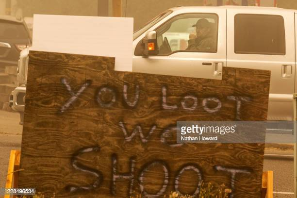 A driver gestures behind a sign warning against looting on September 13 2020 in Sublimity Oregon Multiple wildfires grew by hundreds of thousands of...