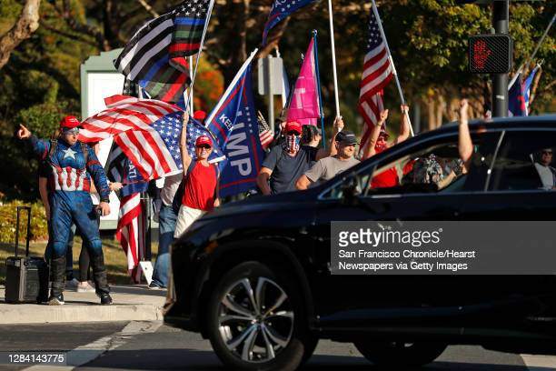 """Driver gives a thumbs down as supporters of US president Donald Trump take part in a """"Trump Town USA Rally"""" at the intersection of Crow Canyon Road..."""