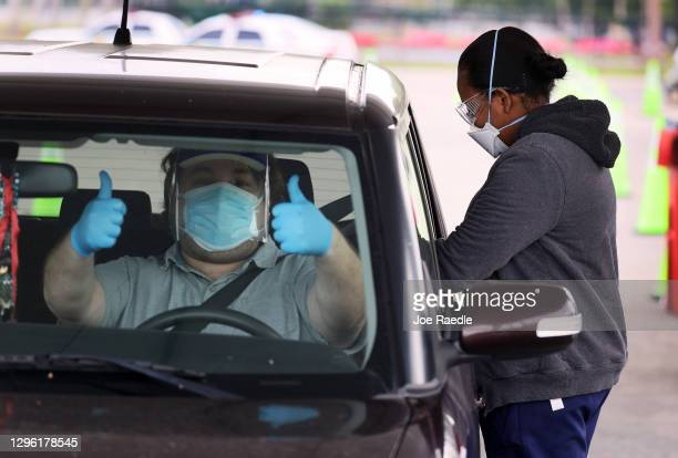 Driver gives a thumbs up as his passenger is given a COVID-19 vaccination by a healthcare worker at a drive-thru site at Tropical Park on January 13,...