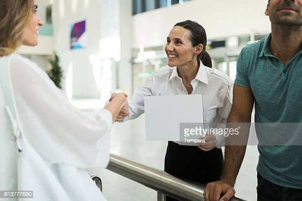 driver greeting business woman with a sign on arrival terminal. - identity stock photos and pictures