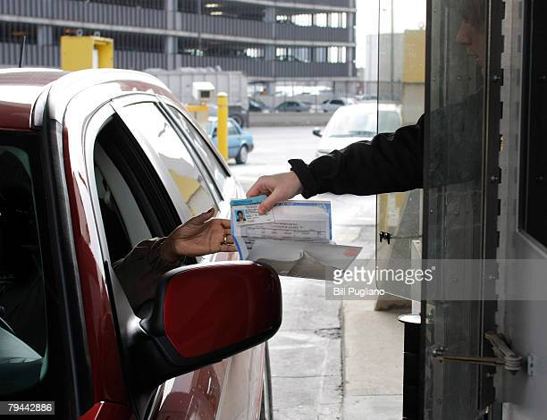 A driver hands her driver's license and birth certificate as proof of citizenship to a US Customs Border Protection agent at the Detroit/Windsor...