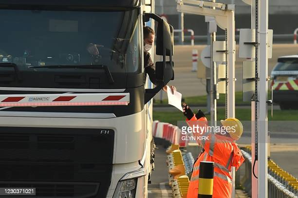 Driver hands out documents for checking at the 'pit stop' for documentation checks before heading to passport control at the Eurotunnel terminal at...