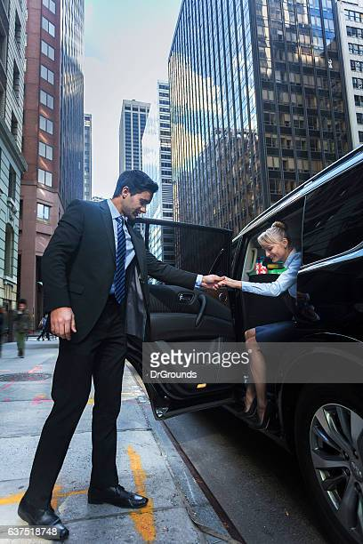 Driver helping passanger out of luxury car