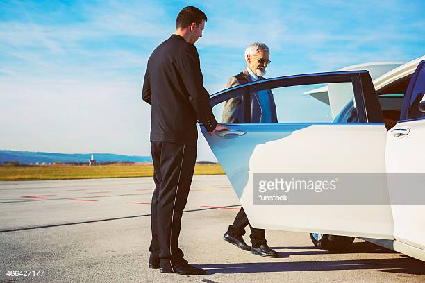 Driver helping senior adult into limousine at airport