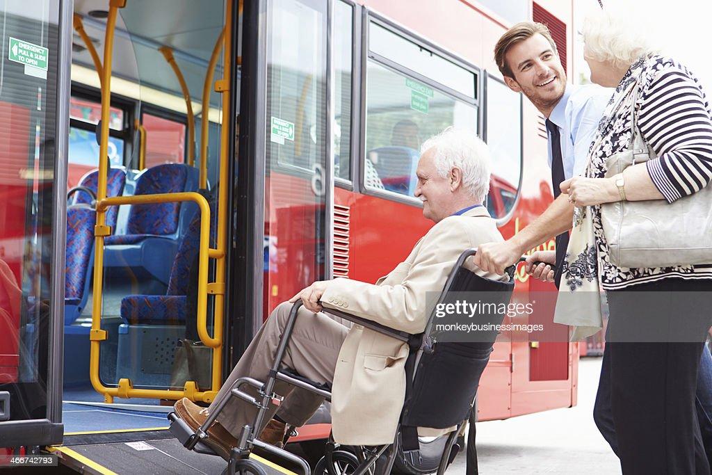 Controlador ajudando Casal Idoso de autocarro através da Rampa para Cadeira de Rodas : Foto de stock