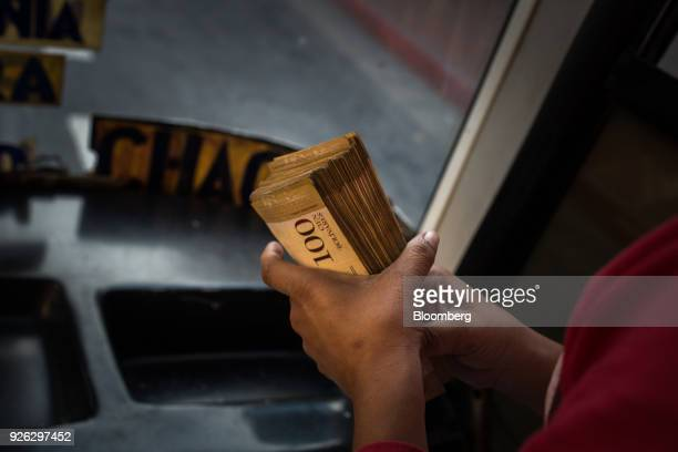 A driver holds a stack of Bolivar banknotes on a public bus in Caracas Venezuela on Thursday March 1 2018 InhyperinflationaryVenezuela paper money...