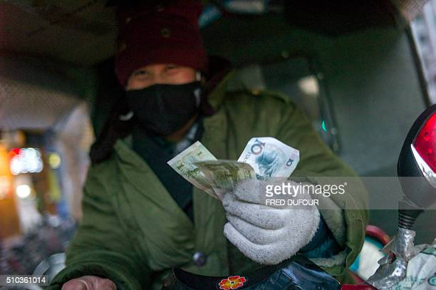 A driver holds up his change after a fair in Beijing on February 15 2016 Chinese trade slumped in January authorities said on February 15 as both...