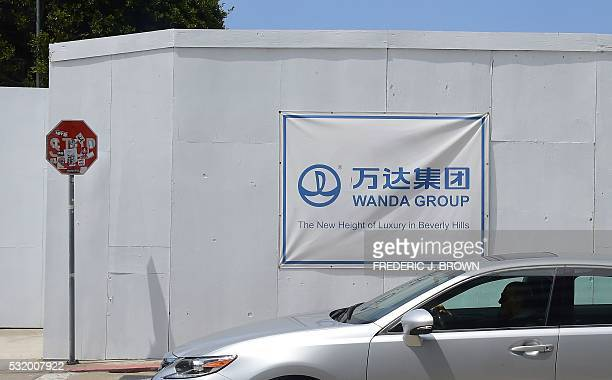 Driver in a BMW passes a Wanda Group banner on a construction site at 9900 Wilshire Boulevard in Beverly Hills, California, right beside the Beverly...