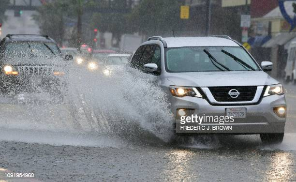 A driver in a vehicle hits water on a partially flooded street in Los Angeles California on January 31 as heavy rains hit southern California...