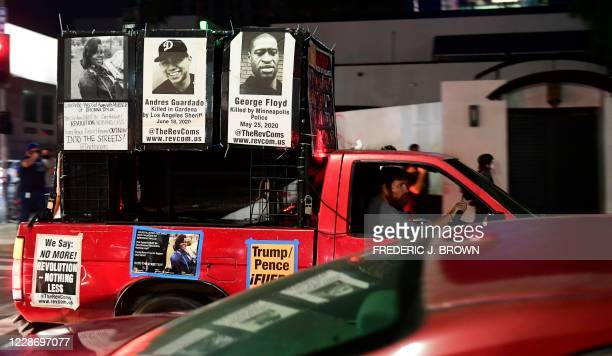 A driver in a vehicle joining protesters displays photos of Breonna Taylor Andres Guardado and George Floyd all killed by law enforcement personel...