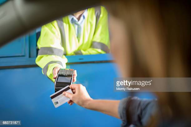Driver in car paying toll booth using contactless card payment technology, close up