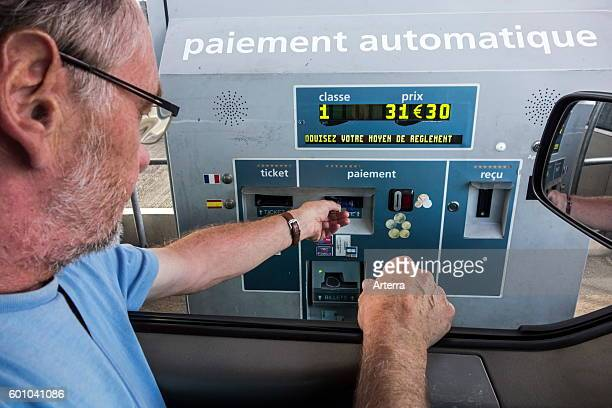 Driver in car paying with credit card at automatic / electronic toll collection booth on French highway