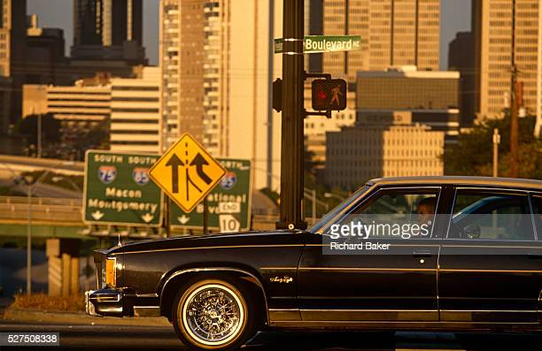 A driver in his gasguzzling car and in the background the skyline of downtown Atlanta Stopped at a traffic light with the cityscape of this American...