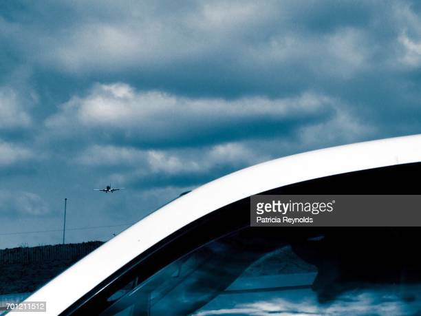 Driver in white vehicle on CA freeway and plane landing at LAX are seen in this photo.