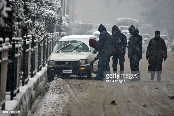 A driver inspects his car which skidded off the road during heavy snowfall in Srinagar Indian administered Kashmir Fresh snowfall began in Kashmir...