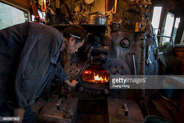 A driver is checking the coal furnace of the steam locomotive Fuxin located in China's northeast Liaoning Province which had the biggest open cast...