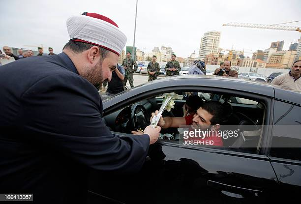 Driver is offered a flower by a cleric during a gathering of clerics representing the various Lebanese religious communities for peace in central...