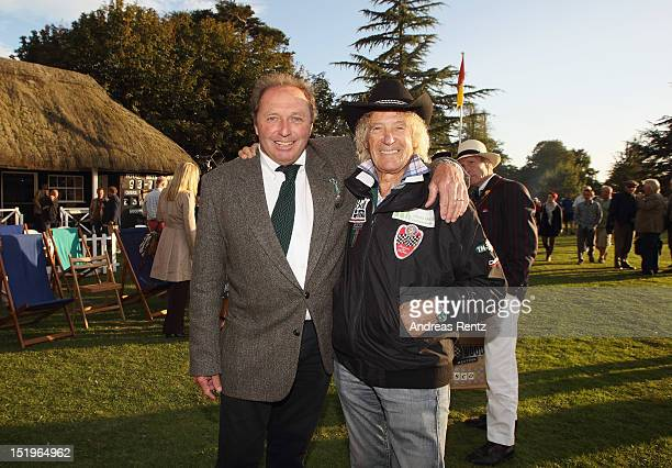 Driver Jochen Mass of Meilenwerk Historic Racing chats with driver Arturo Merzario at the Goodwood Revival 2012 cricket match at the Goodwood House...