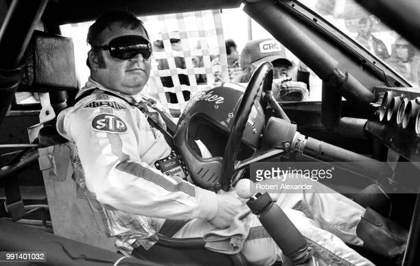 NASCAR driver Joe Booher sits in his car as he waits for his turn to attempt to qualify for the 1982 Daytona 500 at Daytona International Speedway in...