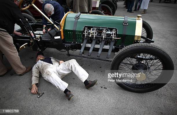 Driver John Dennis lies under his 1907 Berliet/Curtiss Racer as he attempts to fix a fault at The Brooklands Double Twelve Motorsport Festival on...