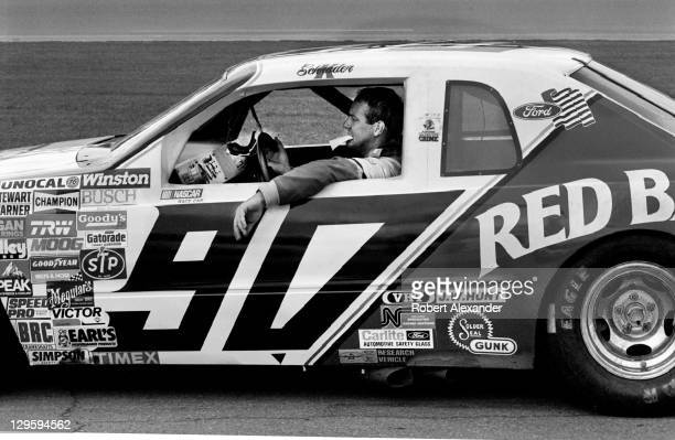 NASCAR driver Ken Schrader sits in his race car during a practice session for the 1986 Daytona 500 at the Daytona International Speedway on February...