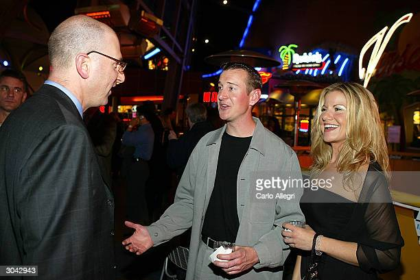 NASCAR driver Kurt Busch and guest Eva Bryan speak with Greg Foster IMAX president of filmed entertainment at the after party of Warner Brothers...
