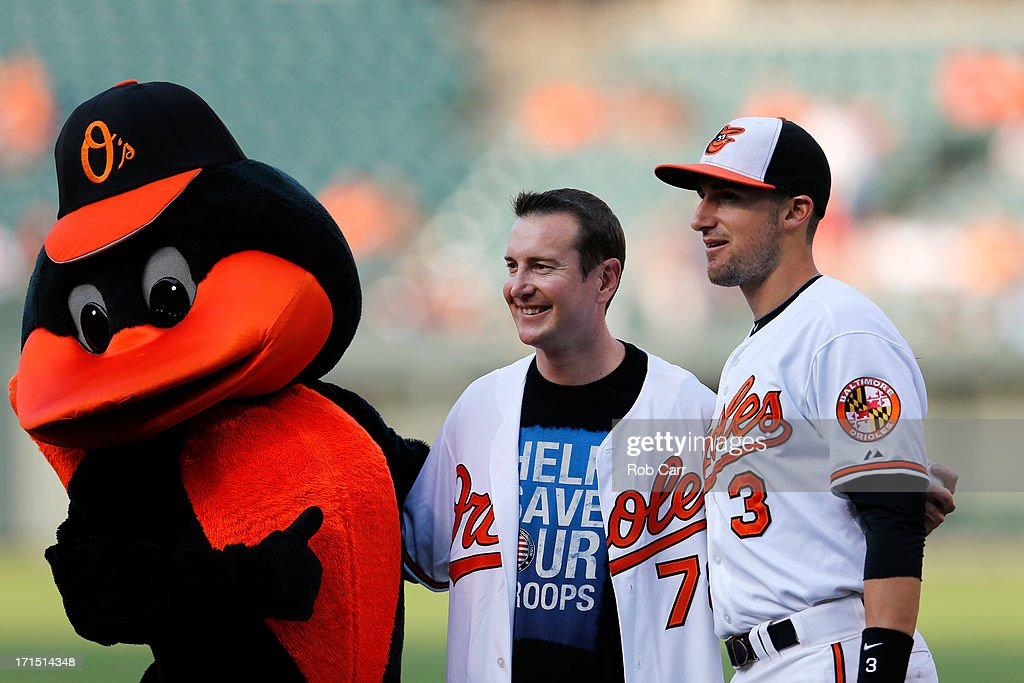 NASCAR driver Kurt Busch of the #78 Furniture Row Racing Chevrolet, poses with the Oriole Bird Mascot and Ryan Flaherty #3 of the Baltimore Orioles after throwing out the ceremonial first pitch before the start of the Baltimore Orioles and Cleveland Indians game at Oriole Park at Camden Yards on June 25, 2013 in Baltimore, Maryland.