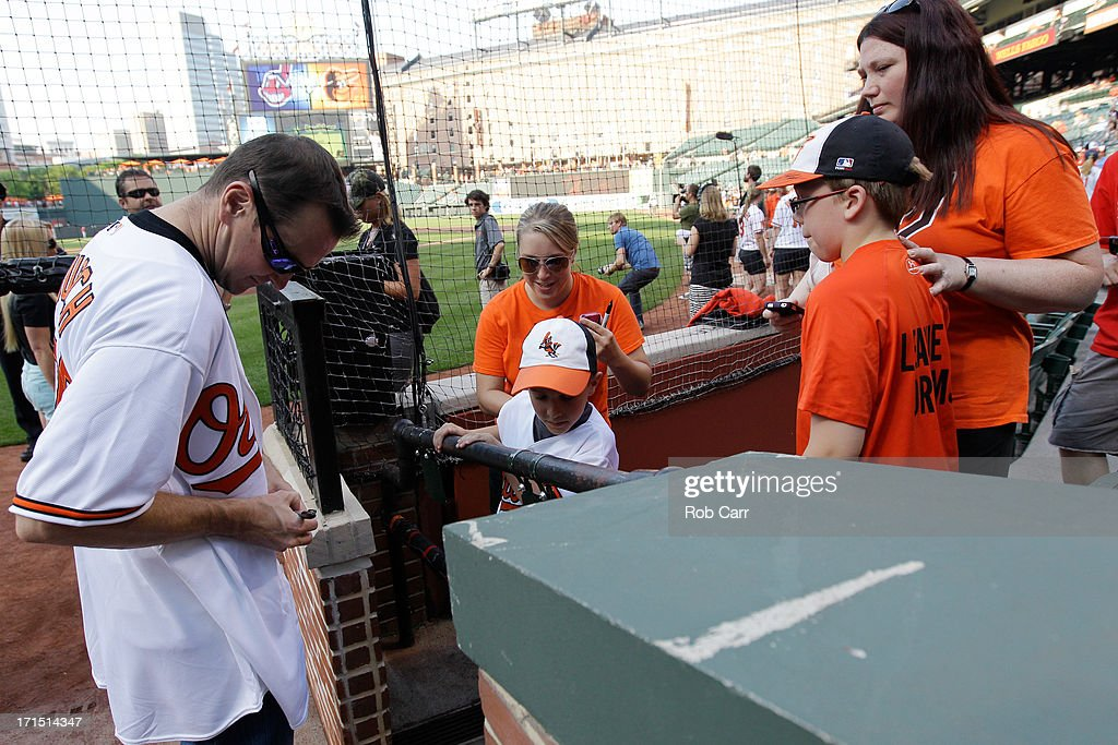 NASCAR driver Kurt Busch of the #78 Furniture Row Racing Chevrolet, signs autographs before throwing out the ceremonial first pitch before the start of the Baltimore Orioles and Cleveland Indians game at Oriole Park at Camden Yards on June 25, 2013 in Baltimore, Maryland.