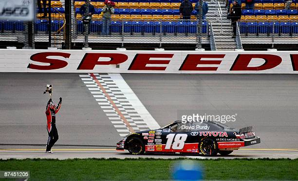 Driver Kyle Busch celebrates with the checkered flag after he won the NASCAR Camping World Series East/West Challenge Long John Silver's 200 on May...