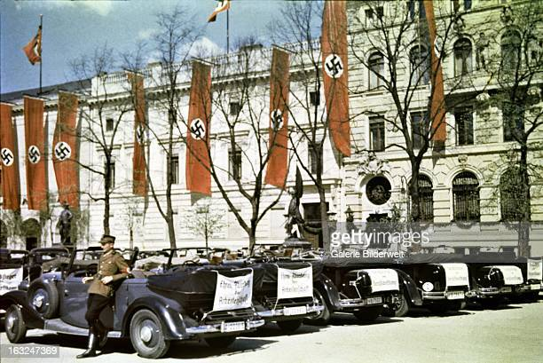 "A driver leans against a state car smoking a cigarette 1st May 1937 On the back of the car is a white cloth stating ""EhrenAbordnung der..."