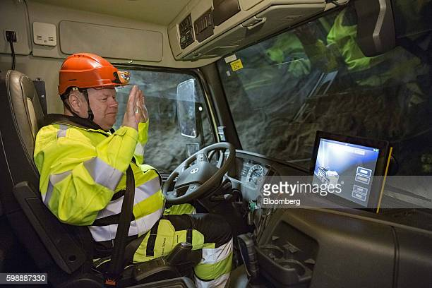 A driver lifts his hands away from the steering wheel of a Volvo Autonomous FMX selfdriving truck manufactured by Volvo Group as it drives through...
