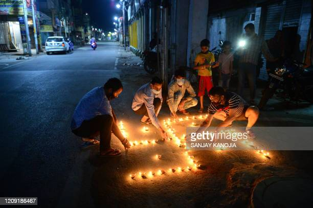 Driver lights his mobile phone to observe a nine-minute vigil called by India's Prime Minister in a show of unity and solidarity in the fight against...