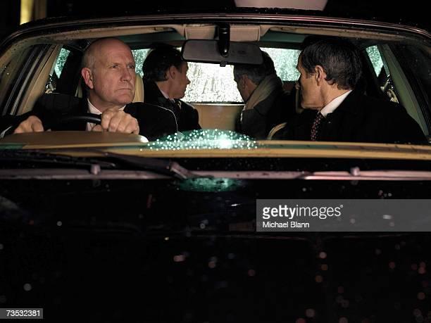 Driver looking in rearview mirror, men looking through rear window