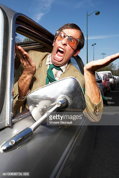 Driver looking out car window and yelling