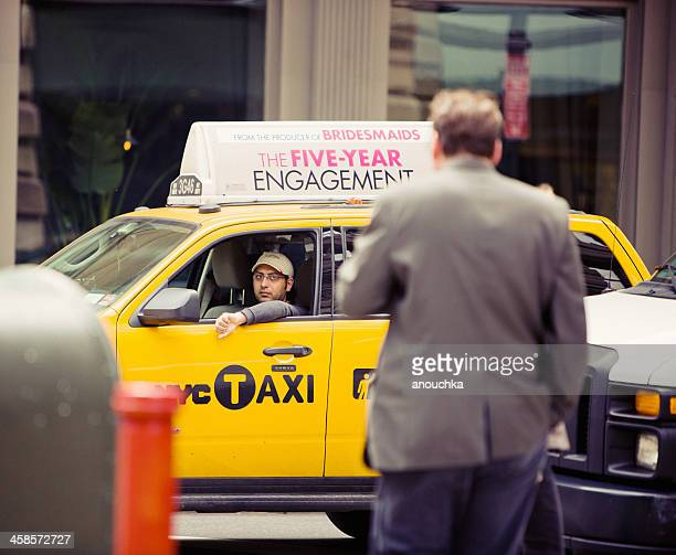 driver looking out of traditional yellow taxi, new york - taxi driver stock photos and pictures