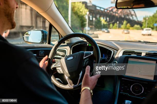 A driver looks from an Uber selfdriving car on September 13 2016 in Pittsburgh Pennsylvania Uber launched a groundbreaking driverless car service...