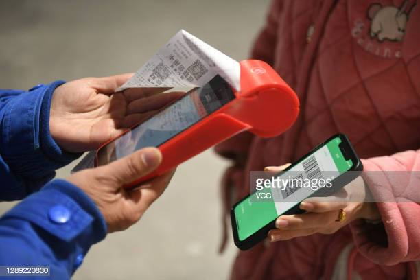 Driver makes a payment using a Wechat QR payment code on her smartphone at a gas station of China Petrochemical Corporation on December 3, 2020 in...