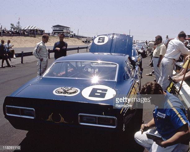 Driver Mark Donohue talks with car owner Roger Penske as the Sunoco crew works on their Chevrolet Camaro on pit road prior to an SCCA TransAm race...