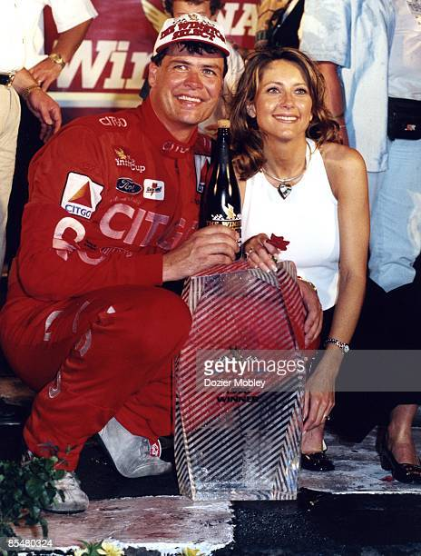 Driver Michael Waltrip smiles with trophy and wife Buffy Waltrip after winning the 1996 The Winston Select race on May 20 1996 at the Charlotte Motor...