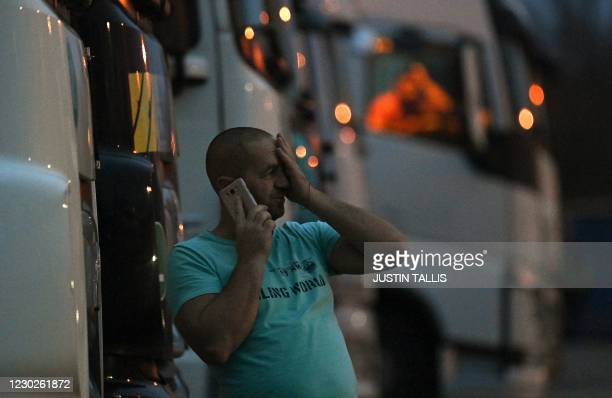 Driver of a freight lorry talk son his phone as he stands outside his cab parked at a truck stop off the M20 leading to Dover, near Folkestone in...