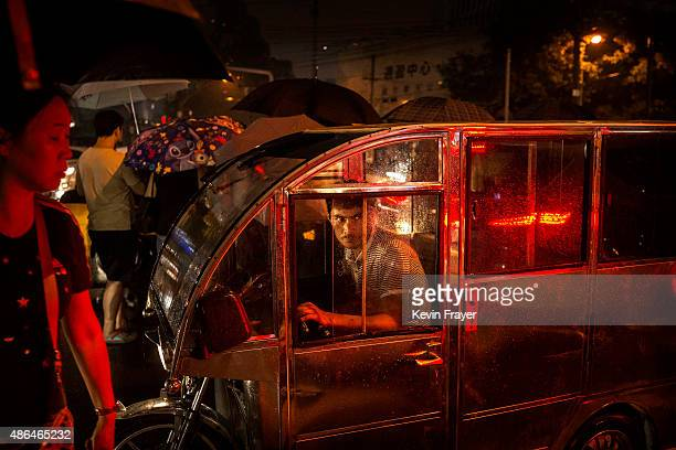 A driver of a threewheeled unofficial motorcycle taxi waits for customers on a rainy evening on September 4 2014 in Beijing China
