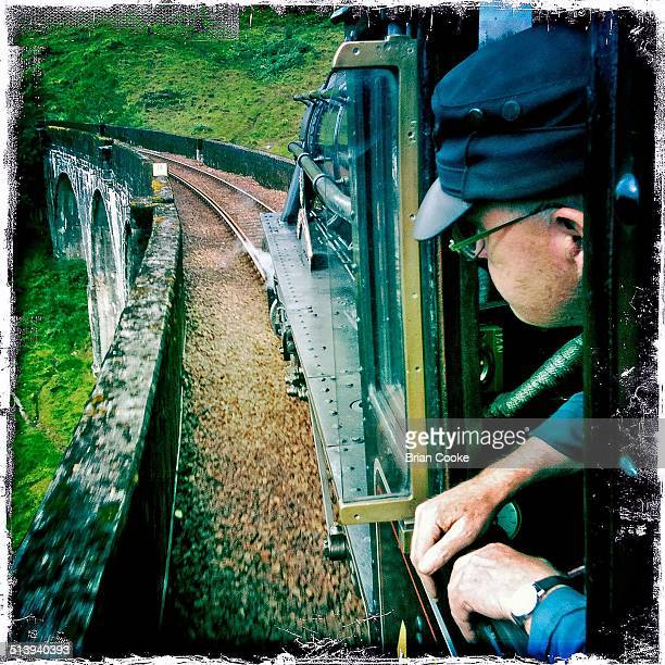 Driver of steam locomotive ex London Midland Scottish Railways Black 5 No 45231 looks out of his cab on Glenfinnan Viaduct which is featured in the...
