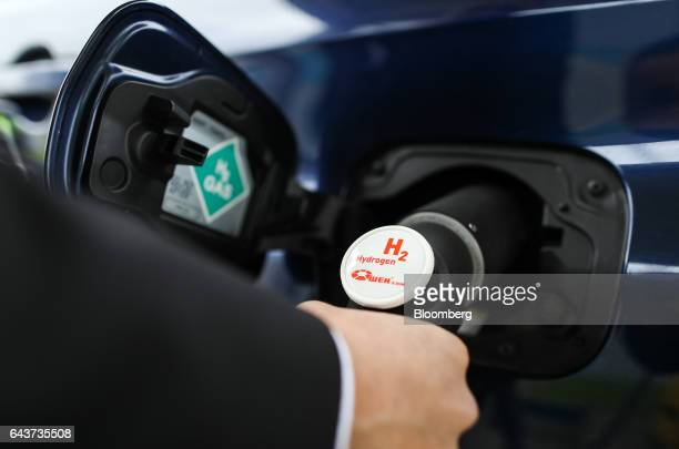 A driver places a hydrogen fuel pump into a Mirai hydrogen fuel powered automobile manufactured by Toyota Motor Corp at Royal Dutch Shell Plc's first...