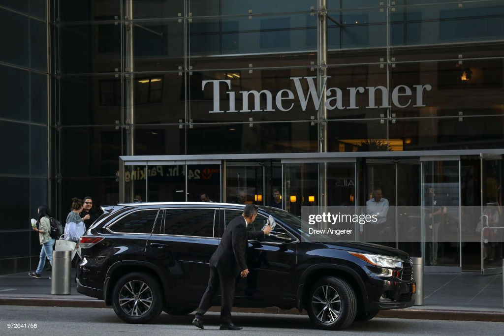 A driver polishes a car outside the Time Warner Center, June 12, 2018 in New York City. A federal judge today said that AT&T can move forward with its $85 billion acquisition of Time Warner, which the U.S. Justice Department had sought to block.