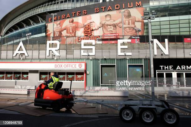 Driver pulls a trailer past the Emirates Stadium in London on March 13, 2020. - The English Premier League suspended all fixtures until April 4 on...