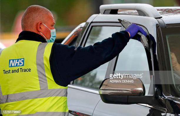 Driver receives a novel coronavirus COVID-19 self-test kit from a worker wearing an NHS Test and Trace branded Hi-Vis jacket at a drive-in testing...